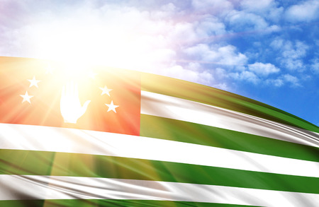 flag of Abkhazia against the blue sky with sun rays. Stock Photo