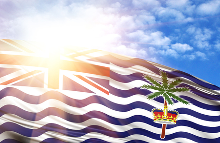 flag of British Territory in the Indian Ocean against the blue sky with sun rays. Stock Photo