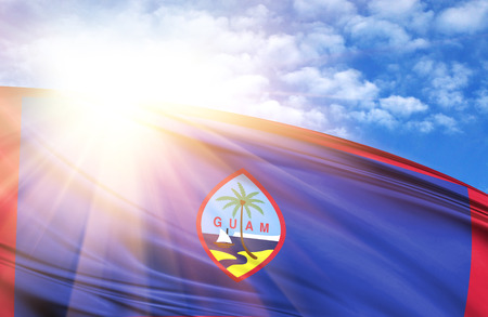 flag of Guam against the blue sky with sun rays. Stock Photo
