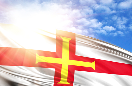 flag of Guernsey against the blue sky with sun rays. Stock Photo