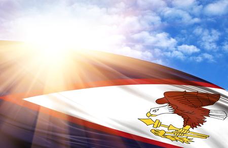 flag of American Samoa against the blue sky with sun rays.