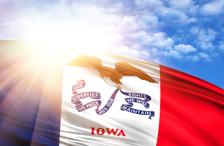 flag of State of Iowa against the blue sky with sun rays.