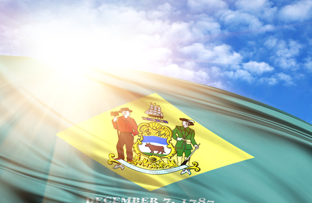 flag of State of Delaware against the blue sky with sun rays.