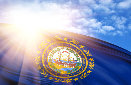 flag of State of New Hampshire against the blue sky with sun rays.