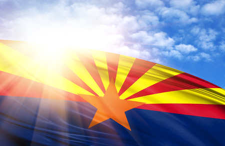 Flag of State of Arizona against the blue sky with sun rays.