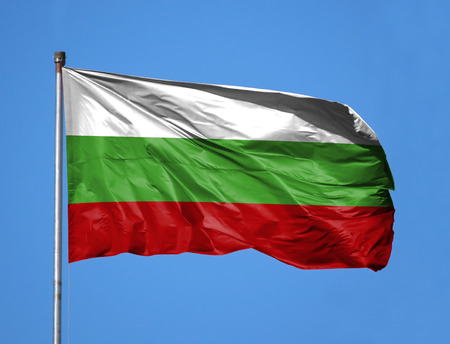 National flag of Bulgaria on a flagpole in front of blue sky. Stock Photo