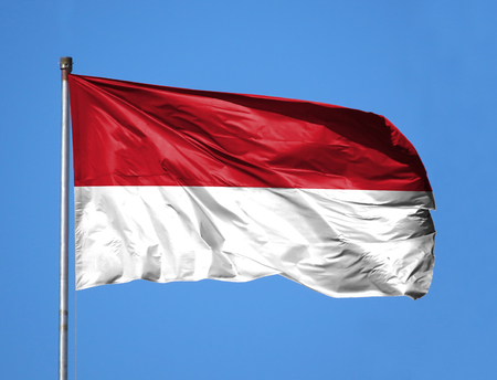 National flag of Indonesia on a flagpole in front of blue sky. Stock Photo