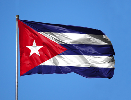 National flag of Cuba on a flagpole in front of blue sky.