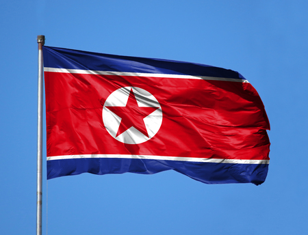 National flag of North Korea on a flagpole in front of blue sky. Foto de archivo