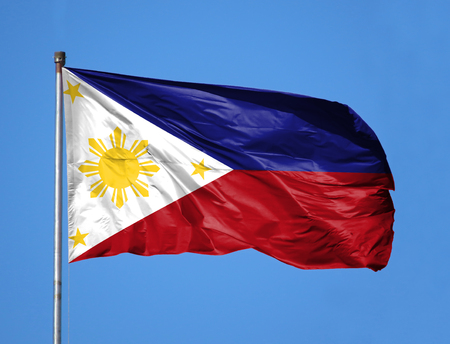 National flag of Philippines on a flagpole in front of blue sky.