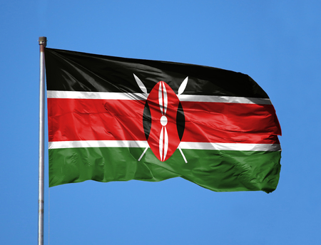 National flag of Kenya on a flagpole in front of blue sky.