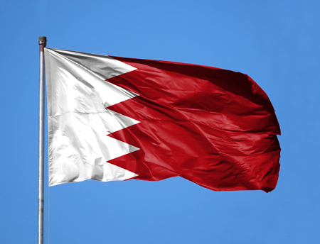 National flag of Bahrain on a flagpole in front of blue sky.