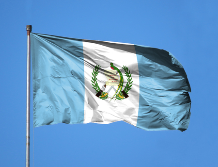 National flag of Guatemala on a flagpole in front of blue sky.