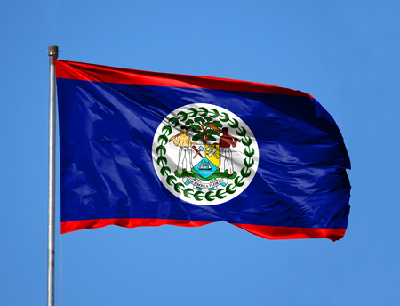 National flag of Belize on a flagpole in front of blue sky.