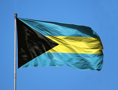 National flag of Bahamas on a flagpole in front of blue sky. Stock Photo