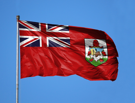 National flag of Bermuda Islands on a flagpole in front of blue sky.