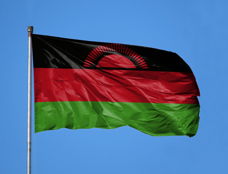 National flag of Malawi on a flagpole in front of blue sky. Stock Photo