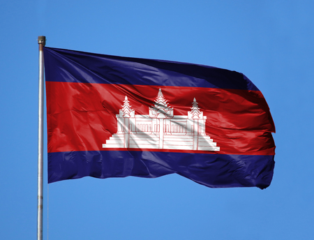 National flag of Cambodia on a flagpole in front of blue sky. Stock Photo