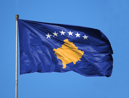 National flag of Kosovo on a flagpole in front of blue sky.