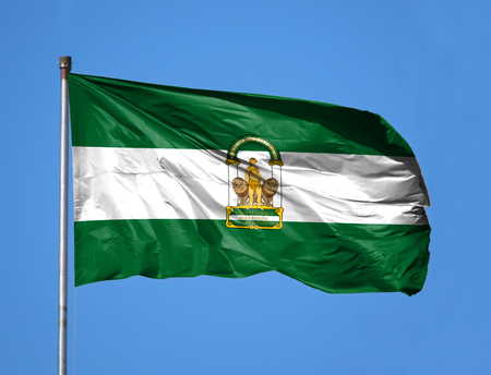 National flag of Andalusia on a flagpole in front of blue sky.