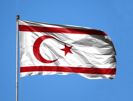 National flag of Turkish Republic of Northern Cyprus on a flagpole in front of blue sky.