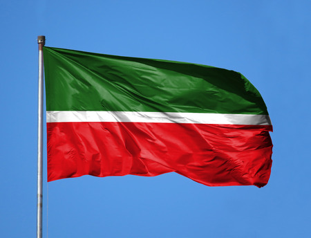 National flag of Tatarstan on a flagpole in front of blue sky.