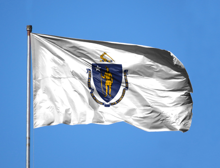 National flag State of Massachusetts on a flagpole in front of blue sky.