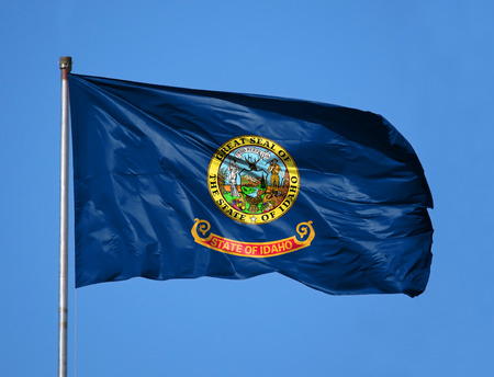 National flag State of Idaho on a flagpole in front of blue sky.