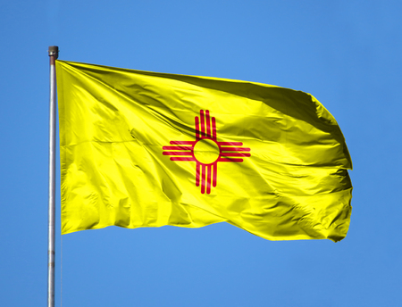 National flag State of New Mexico on a flagpole in front of blue sky.