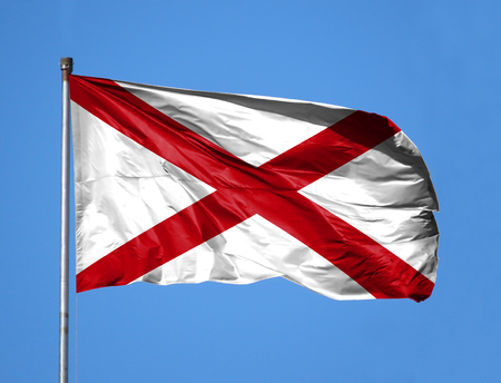 National flag State of Alabama on a flagpole in front of blue sky. Stock Photo