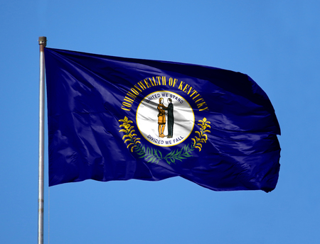 National flag State of Kentucky on a flagpole in front of blue sky.