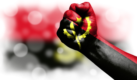 Flag of Angola drawn on male fist, strength,power,concept of conflict. On a blurred background with a good place for your text. Foto de archivo