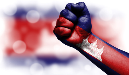 Flag of Cambodia drawn on male fist, strength,power,concept of conflict. On a blurred background with a good place for your text.
