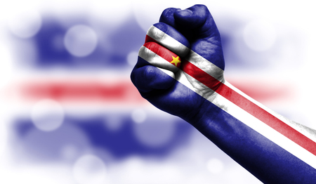 Flag of Cape verde drawn on male fist, strength,power,concept of conflict. On a blurred background with a good place for your text. Stock Photo