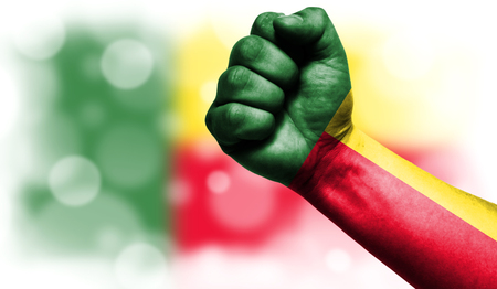 Flag of Benin drawn on male fist, strength,power,concept of conflict. On a blurred background with a good place for your text.