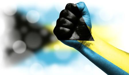 男性の拳、強さ、パワー、紛争の概念に描かれたバハマの旗。あなたのテキストのための良い場所とぼやけた背景に。