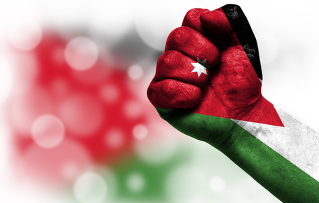 Flag of Jordan painted on male fist, strength,power,concept of conflict. On a blurred background with a good place for your text.