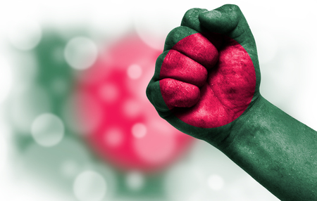 Flag of Bangladesh painted on male fist, strength,power,concept of conflict. On a blurred background with a good place for your text.