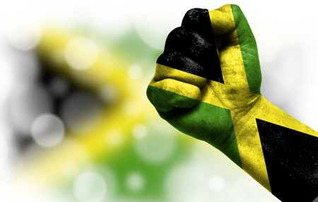 Flag of Jamaica painted on male fist, strength,power,concept of conflict. On a blurred background with a good place for your text. Banco de Imagens