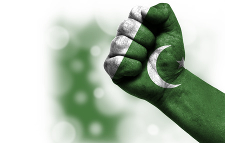 Flag of Pakistan painted on male fist, strength,power,concept of conflict. On a blurred background with a good place for your text.
