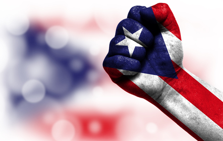 Flag of Puerto Rico painted on male fist, strength,power,concept of conflict. On a blurred background with a good place for your text.