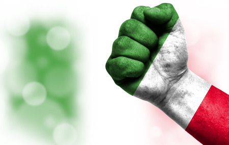 Flag of Italy painted on male fist, strength,power,concept of conflict. On a blurred background with a good place for your text.
