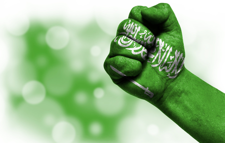 Flag of Saudi Arabia painted on male fist, strength,power,concept of conflict. On a blurred background with a good place for your text. Stock Photo