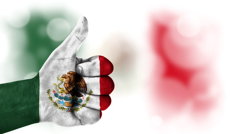 Flag of Mexico drawn on a man's hand with a thumb up, on a blurry background with a good place for text
