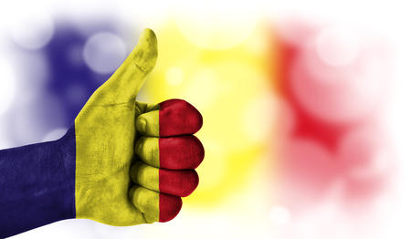 Flag of Romania drawn on a mans hand with a thumb up, on a blurry background with a good place for text