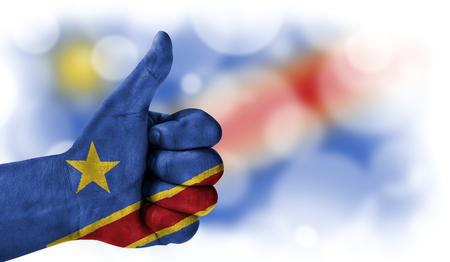Flag of Congo Democratic drawn on a man's hand with a thumb up, on a blurry background with a good place for text