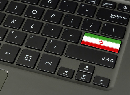 Flag of Iran on laptop keyboard, close-up.