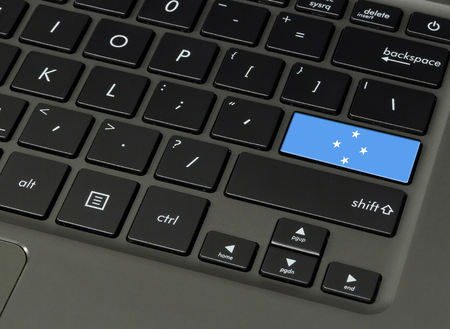 Flag of Micronesia on laptop keyboard, close-up.