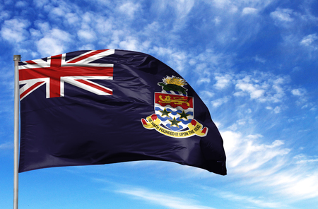 National flag of Cayman islands on a flagpole in front of blue sky. Фото со стока
