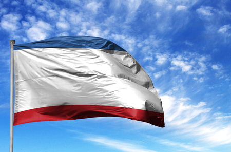 National flag of Crimea on a flagpole in front of blue sky. Stock Photo